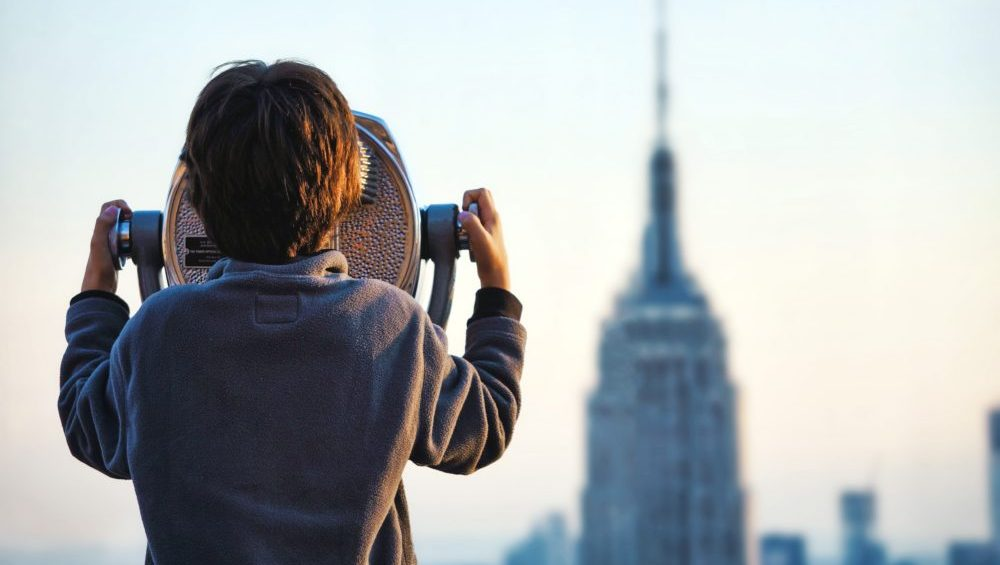 Boy looking through the binoculars at New York city